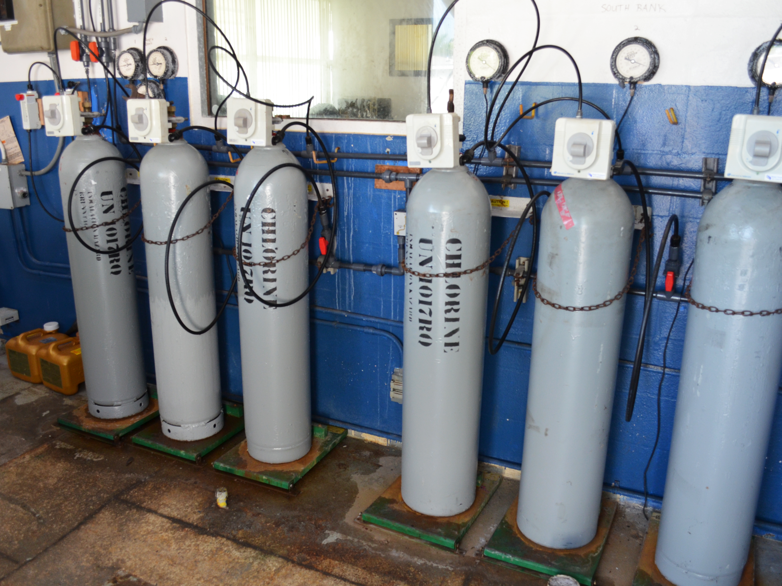 Six silver-colored canisters of chlorine hooked up to the water supply in the water plant.
