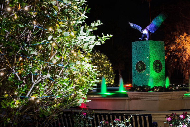 The fountain with an eagle on top at Hunter Memorial Park, lit up with holiday colors