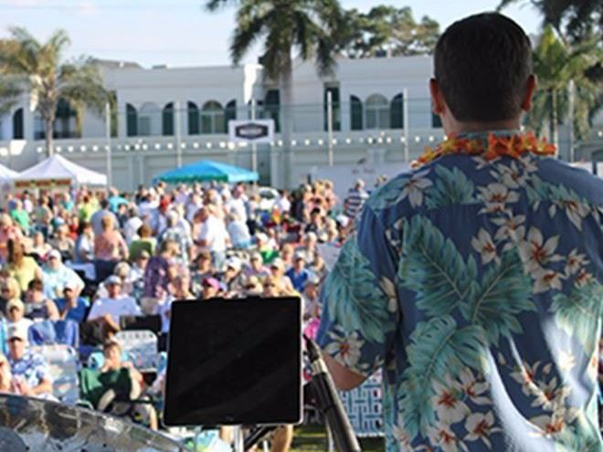 Announcer at a Belleair concert wearing a Hawaiian shirt in front of a crowd of attendees.