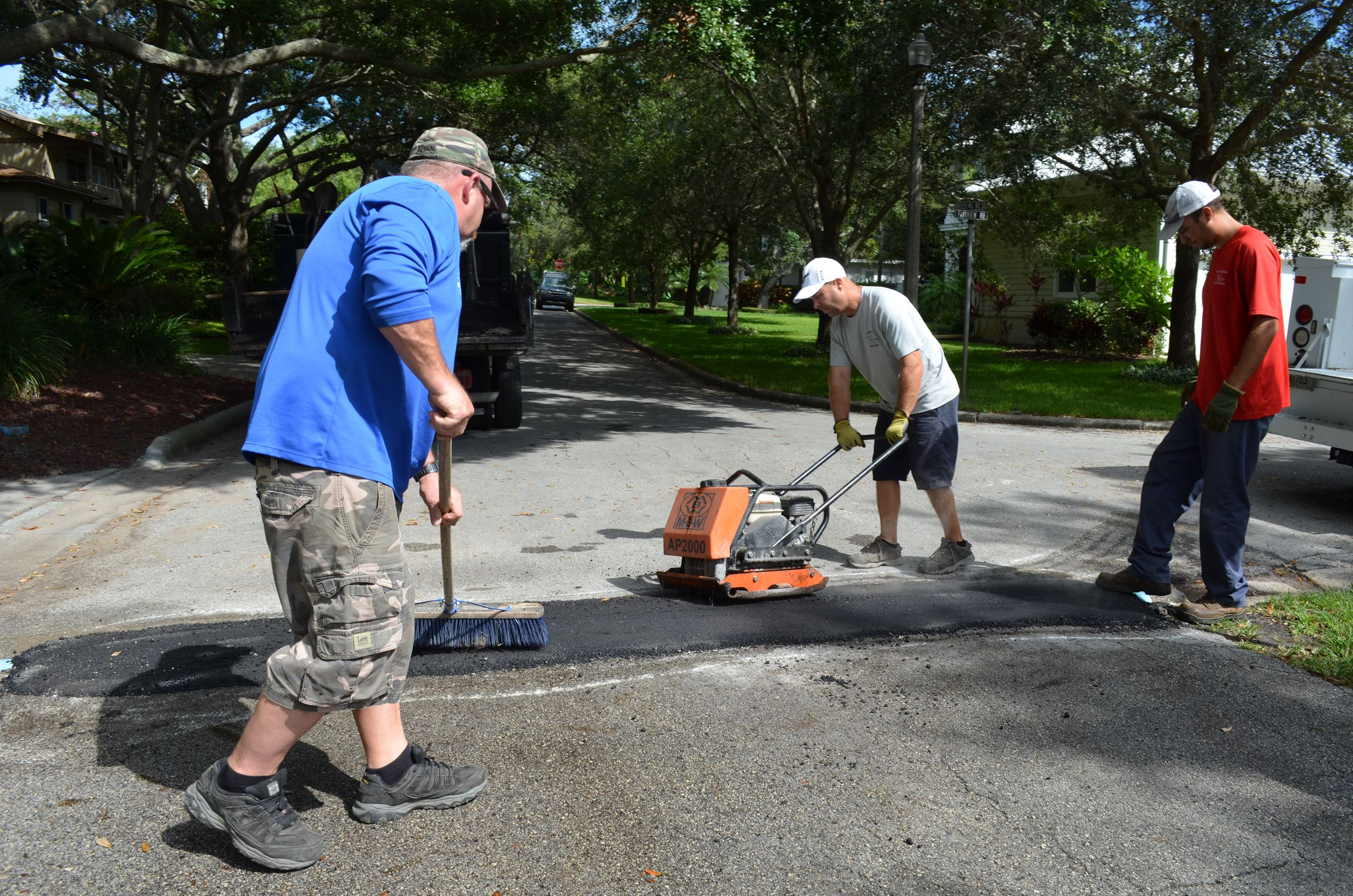 Three men laying asphalt on a street to fill a pothole.