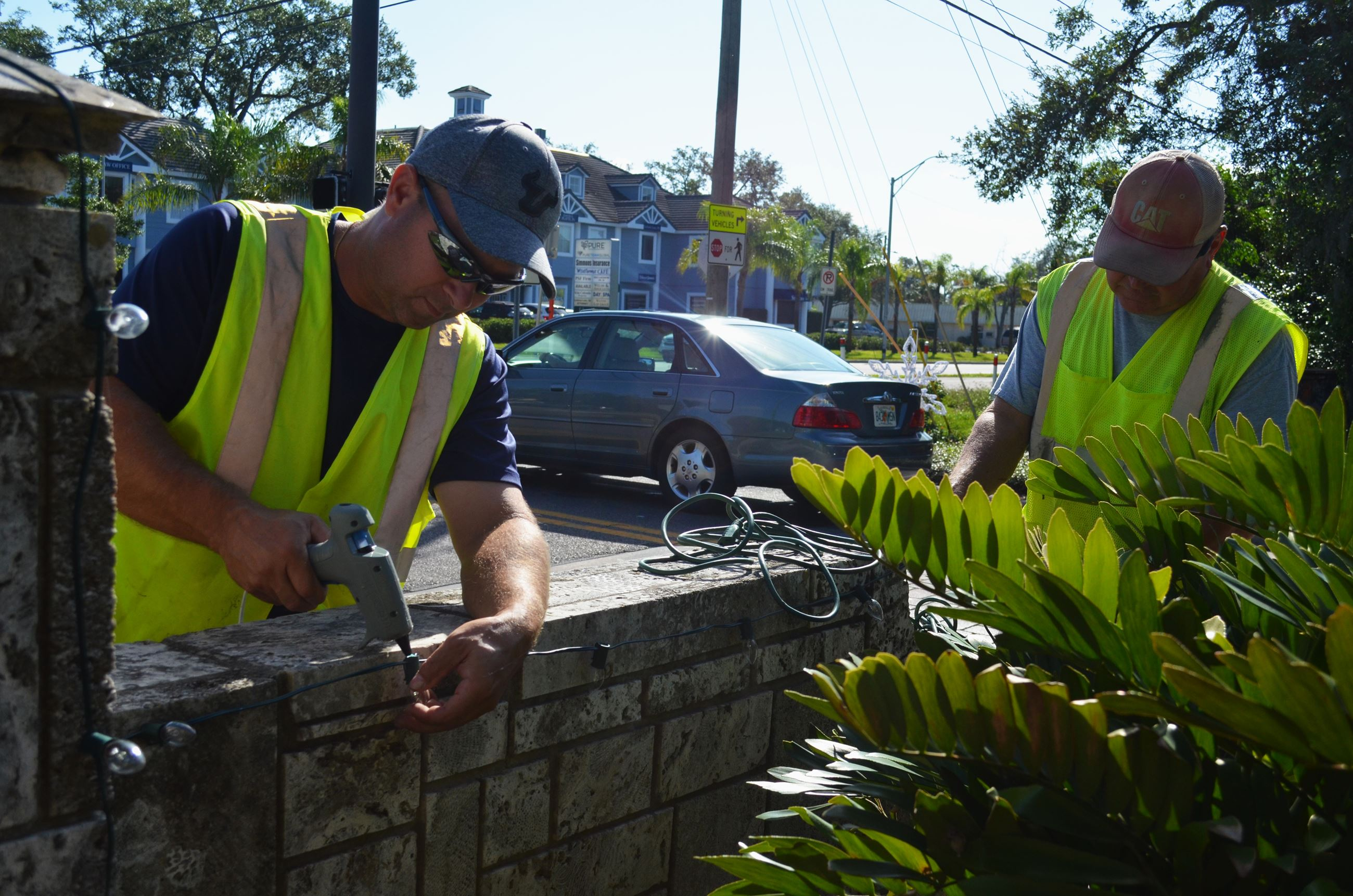 Two men in yellow vests affix holiday lights to a Town of Belleair entrance sign.