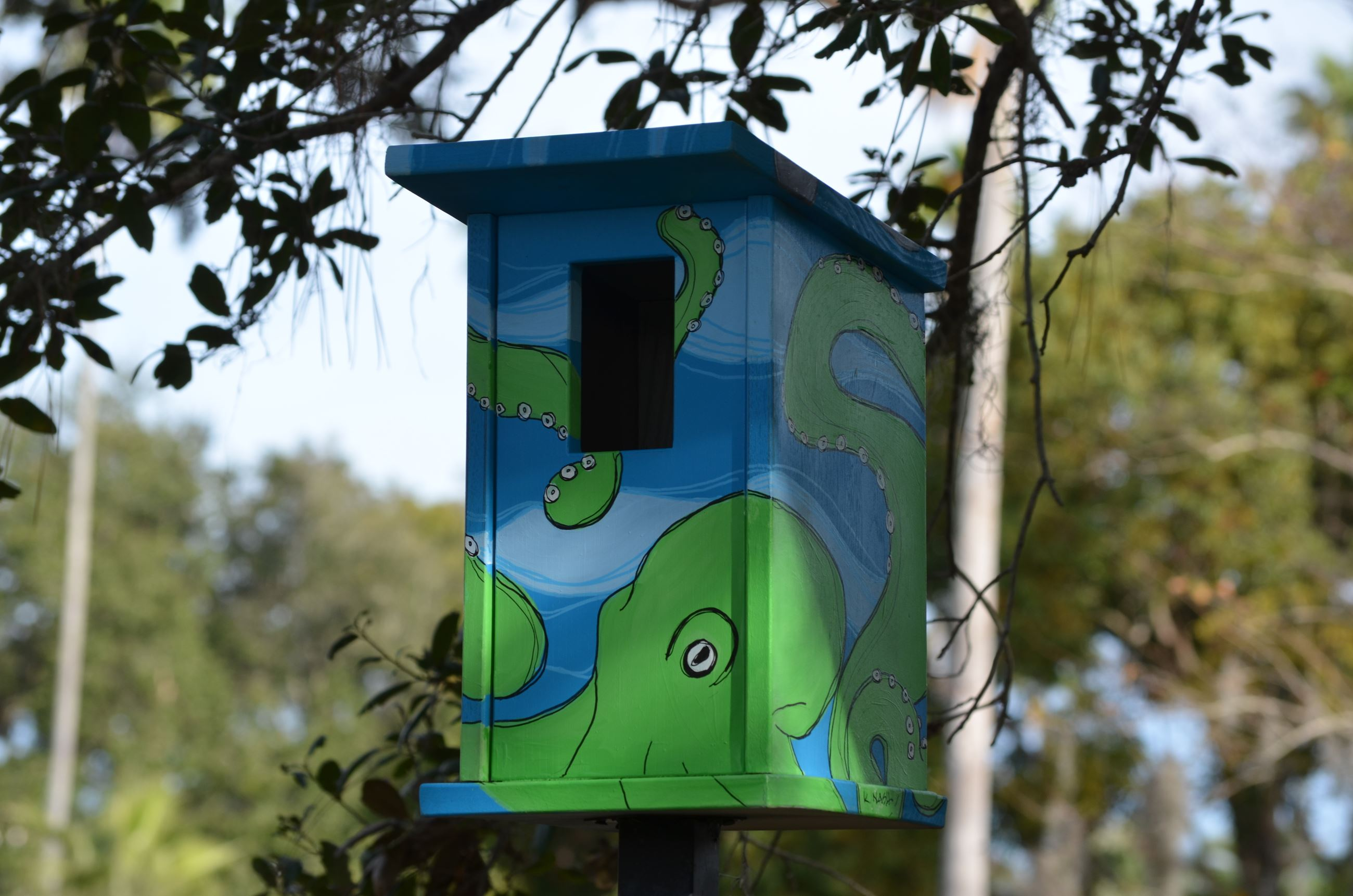 A hand-painted blue birdhouse in Doyle/Wall Park that has a green octopus on it