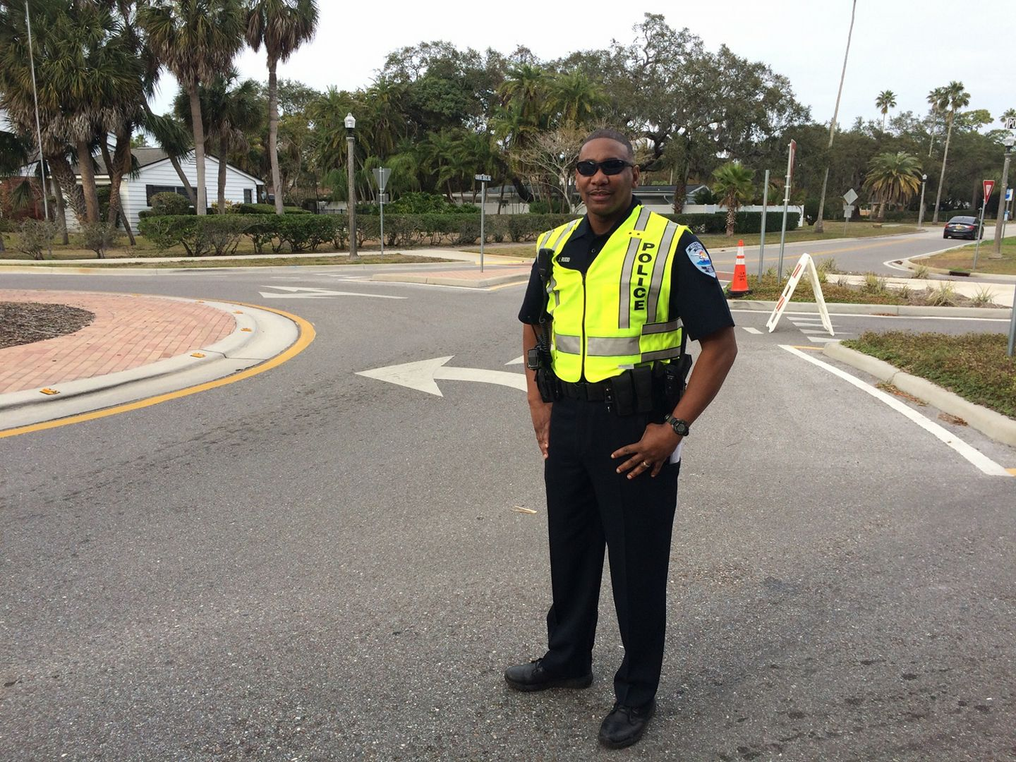 Officer Rudd stands in a street with his safety vest on for his Employee of the Month photo.
