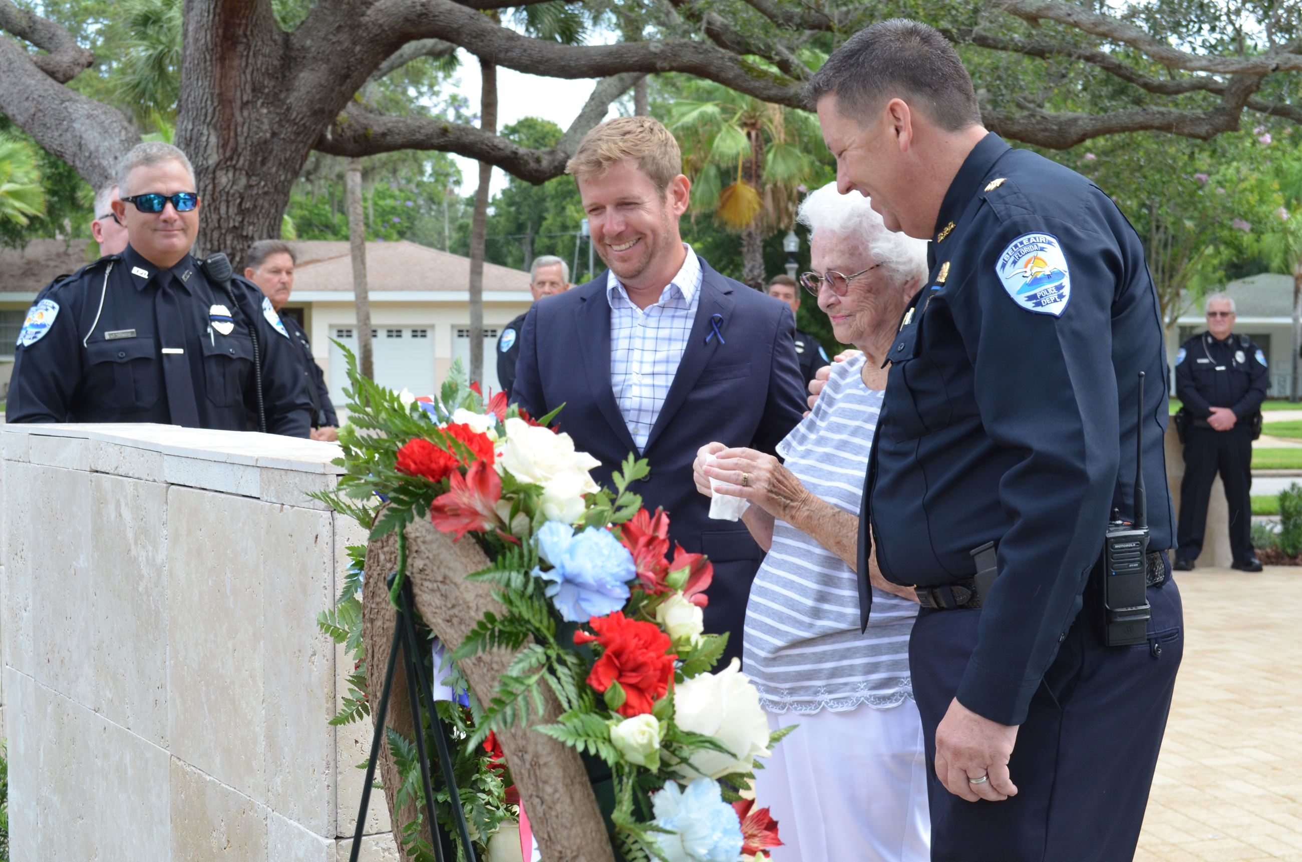 Two Police Officers, Town Employee and Lady looking at memorial plaque in Tackett Park.