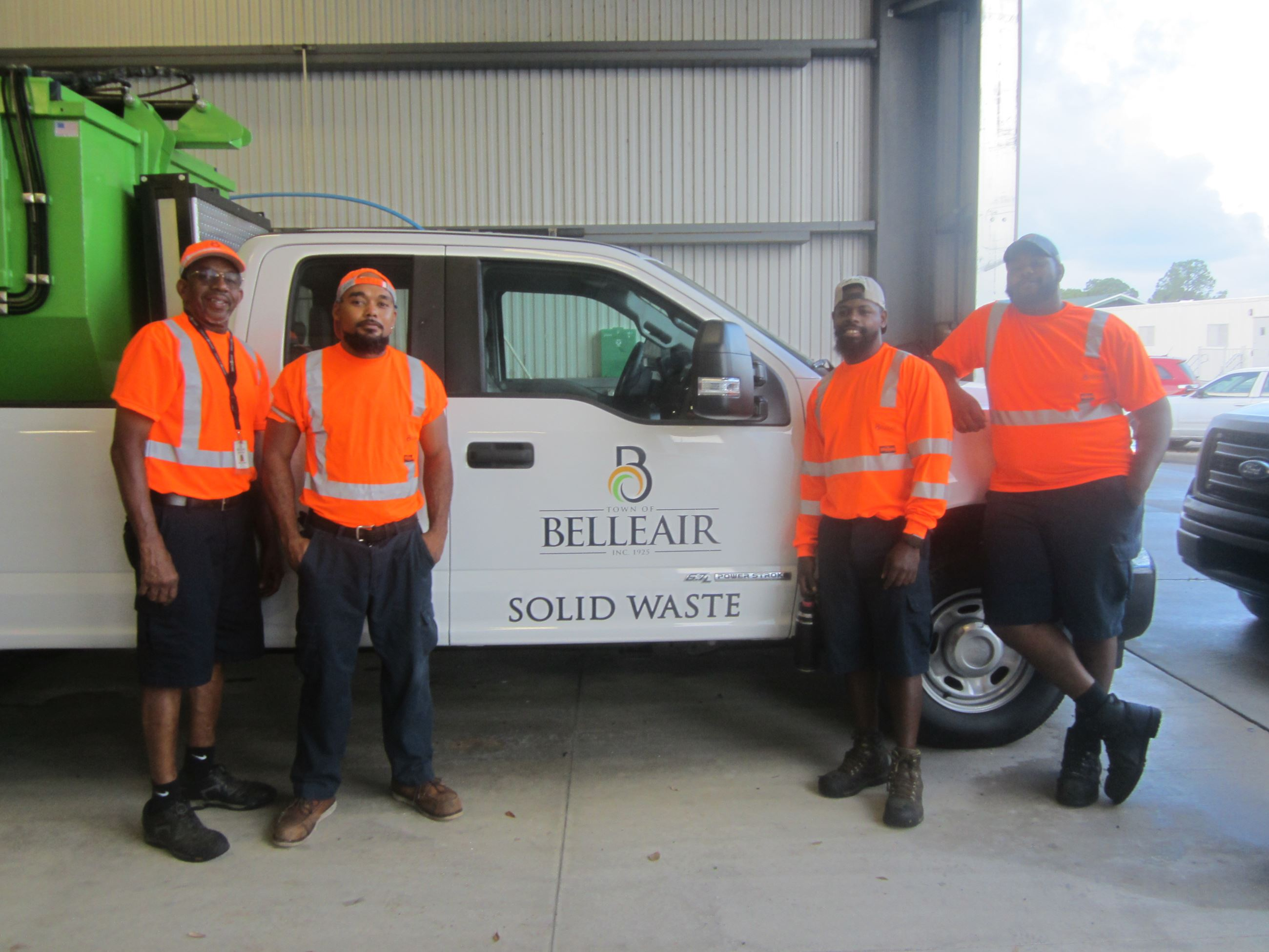 Four members of Belleair's Solid Waste Department smile in front of the Town's satellite picku