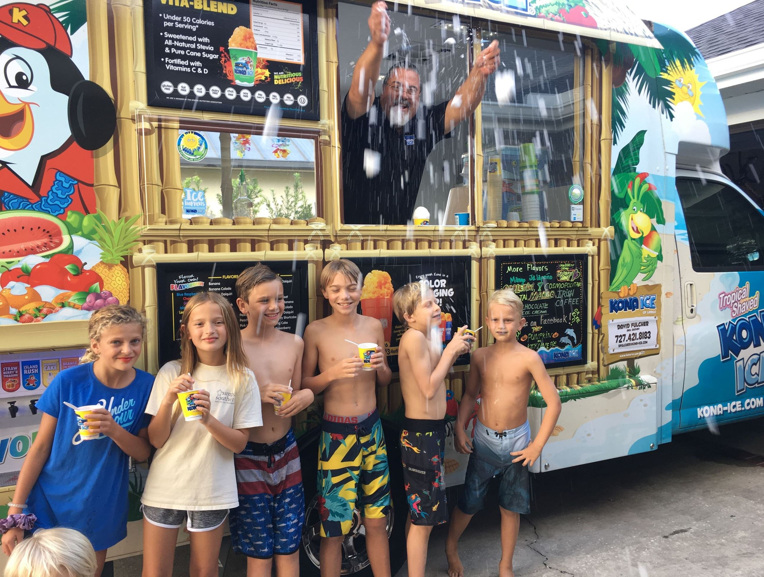 Group of children in front of Kona Ice Truck smiling