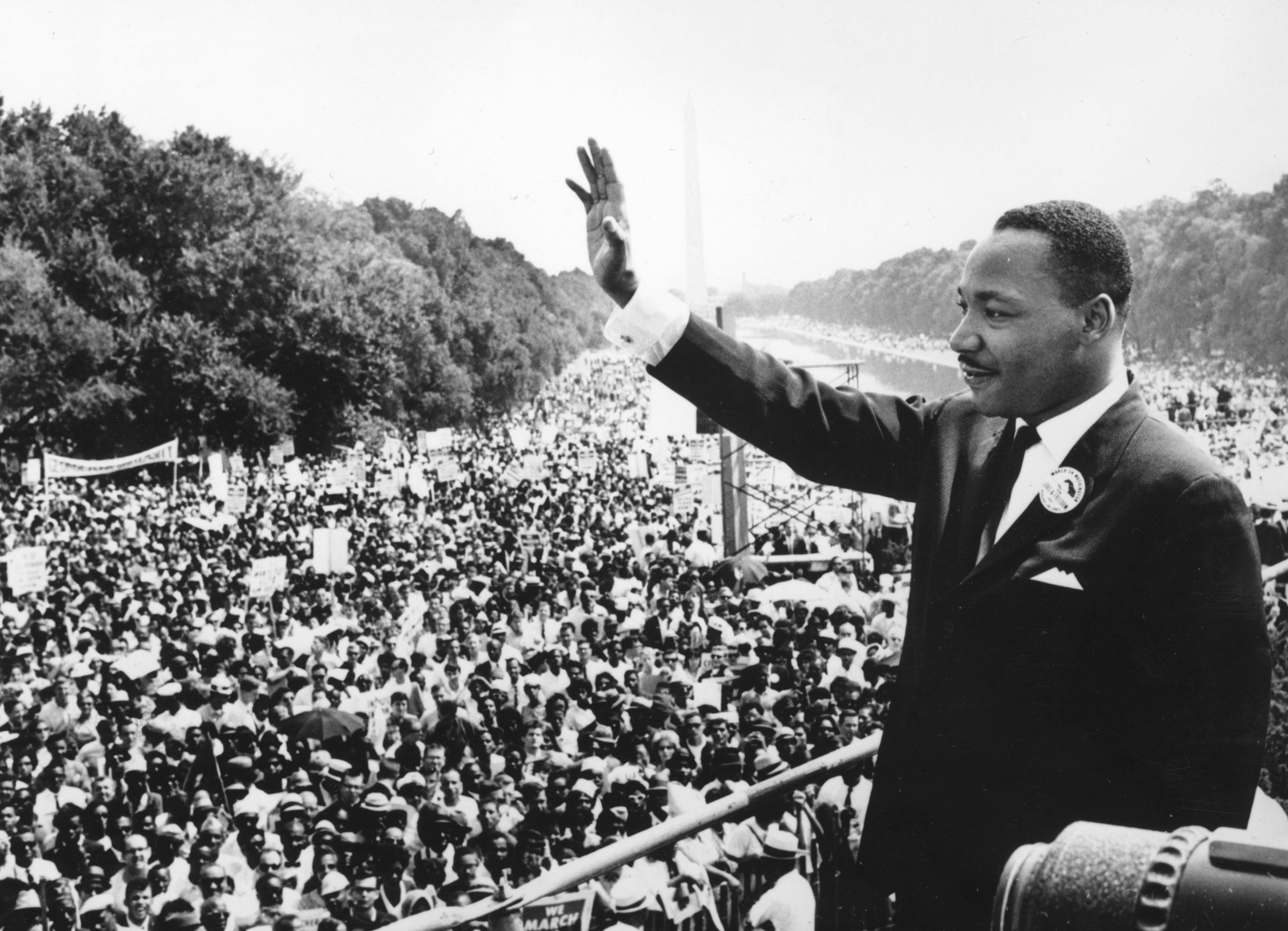 A historic photo of Dr. Martin Luther King Jr. waving in front of a large crowd