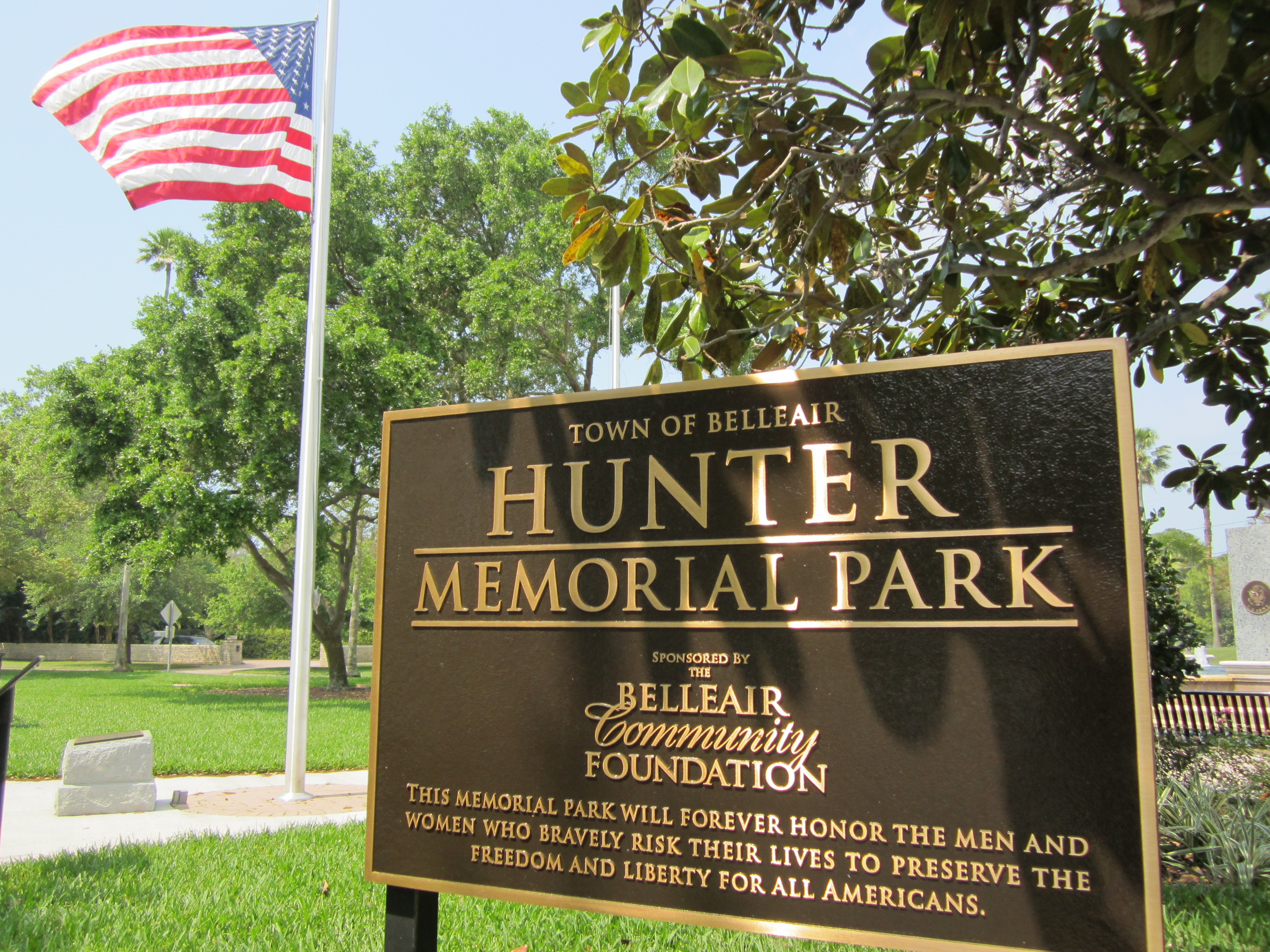 A bronze entrance sign to Hunter Memorial Park that includes the Belleair Community Foundation logo