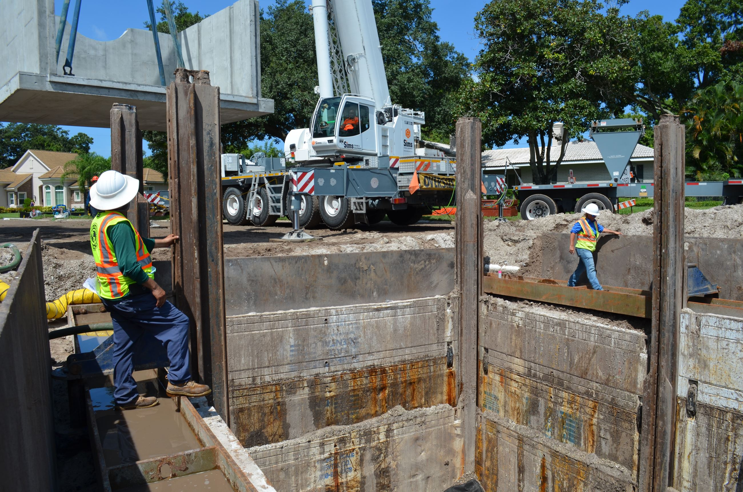 Contractors lower a large, rectangular baffle box base into the ground using a crane as a part of th
