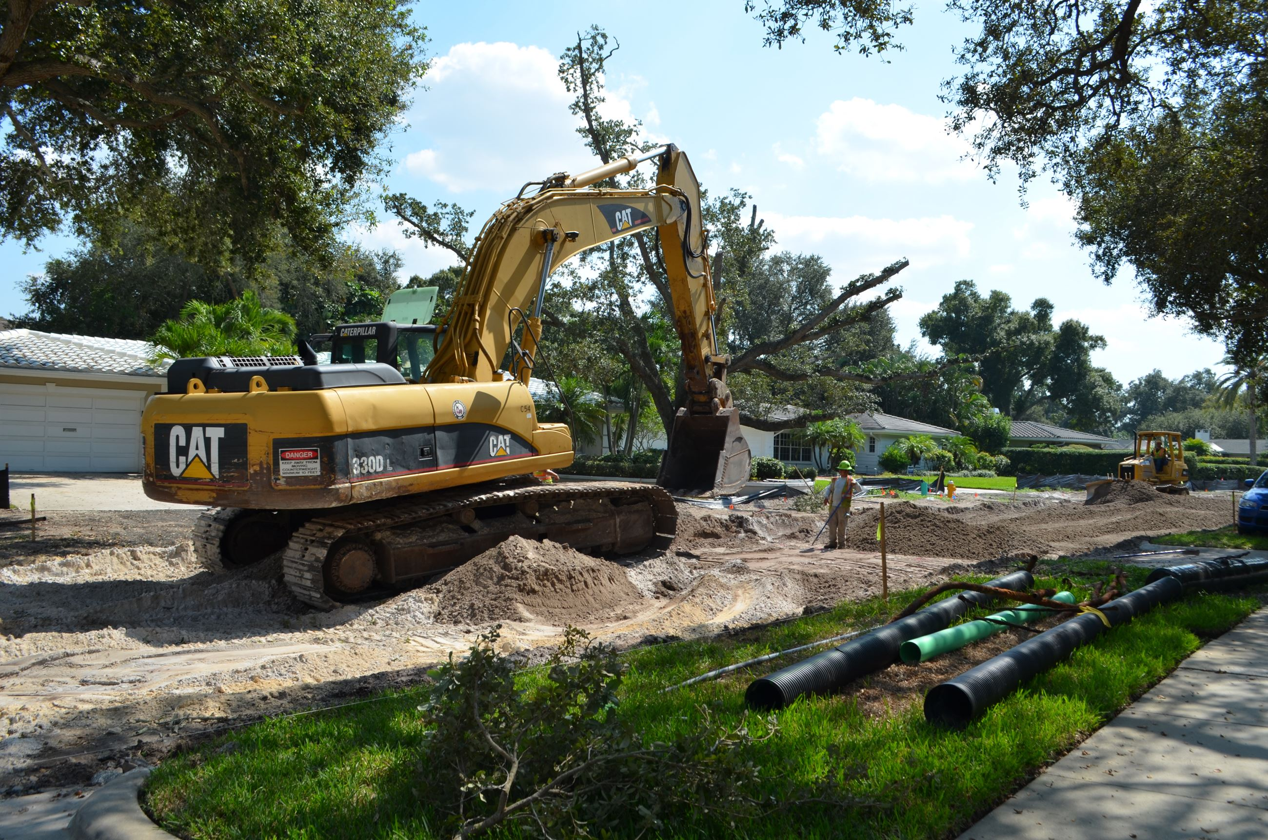 Construction vehicles and employees clear and level dirt on Palmetto Road