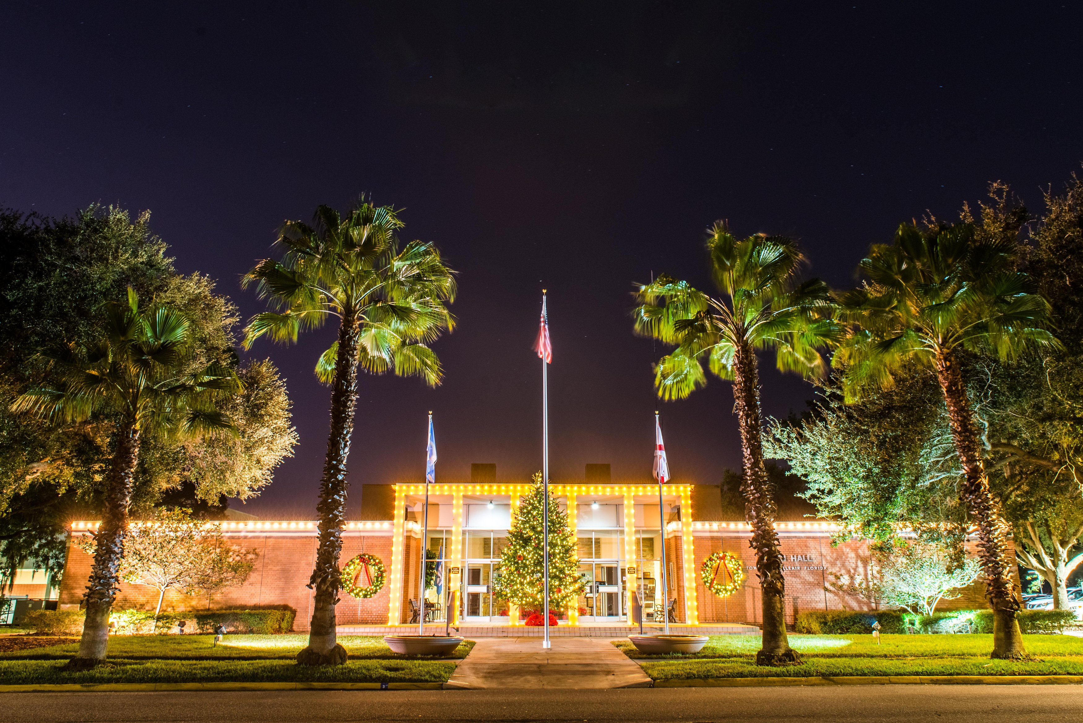 Belleair's Town Hall building light up with holiday lighting from a view across the street