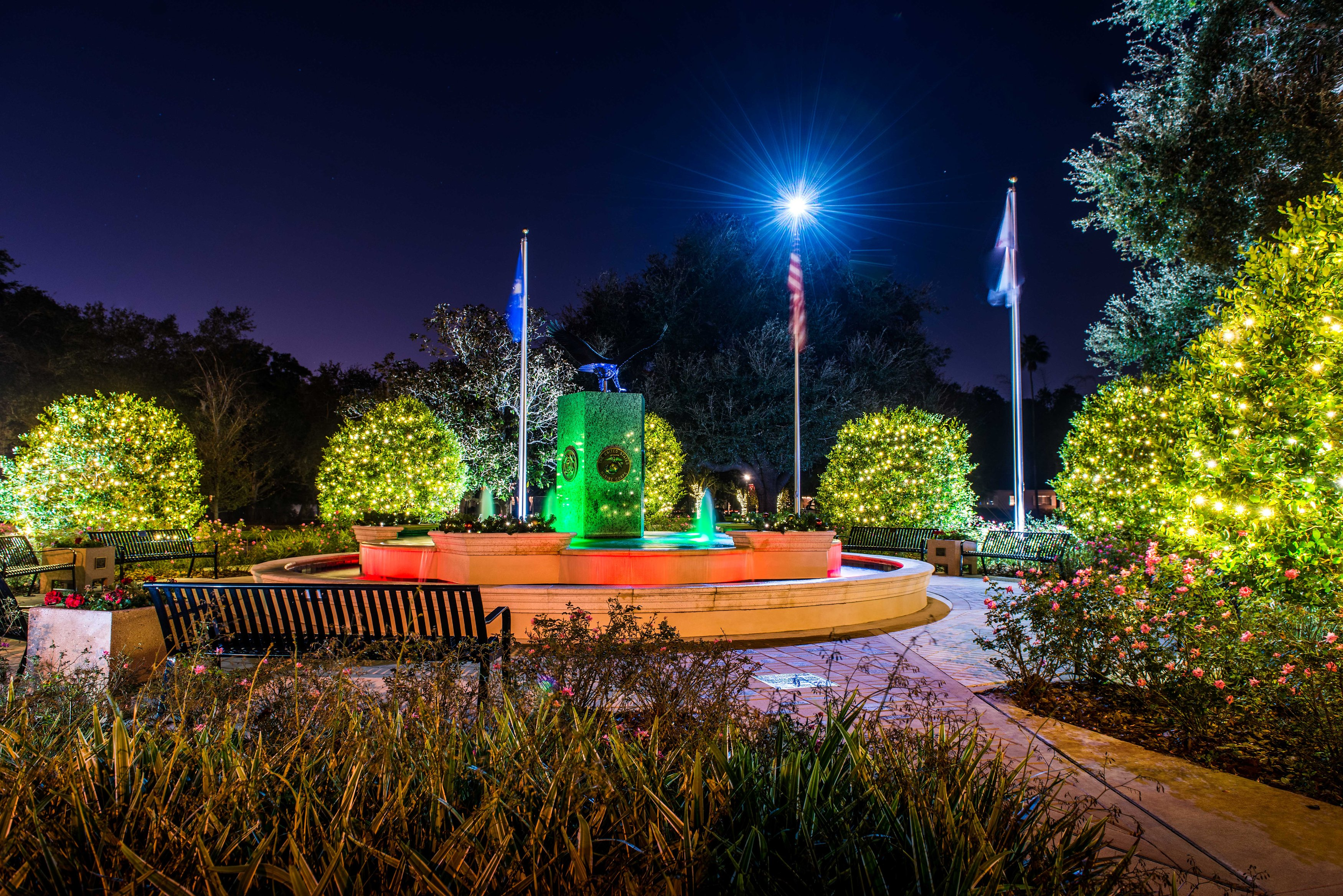 A view of Hunter Memorial Park's fountain, benches, and pavers, lit for the holiday season