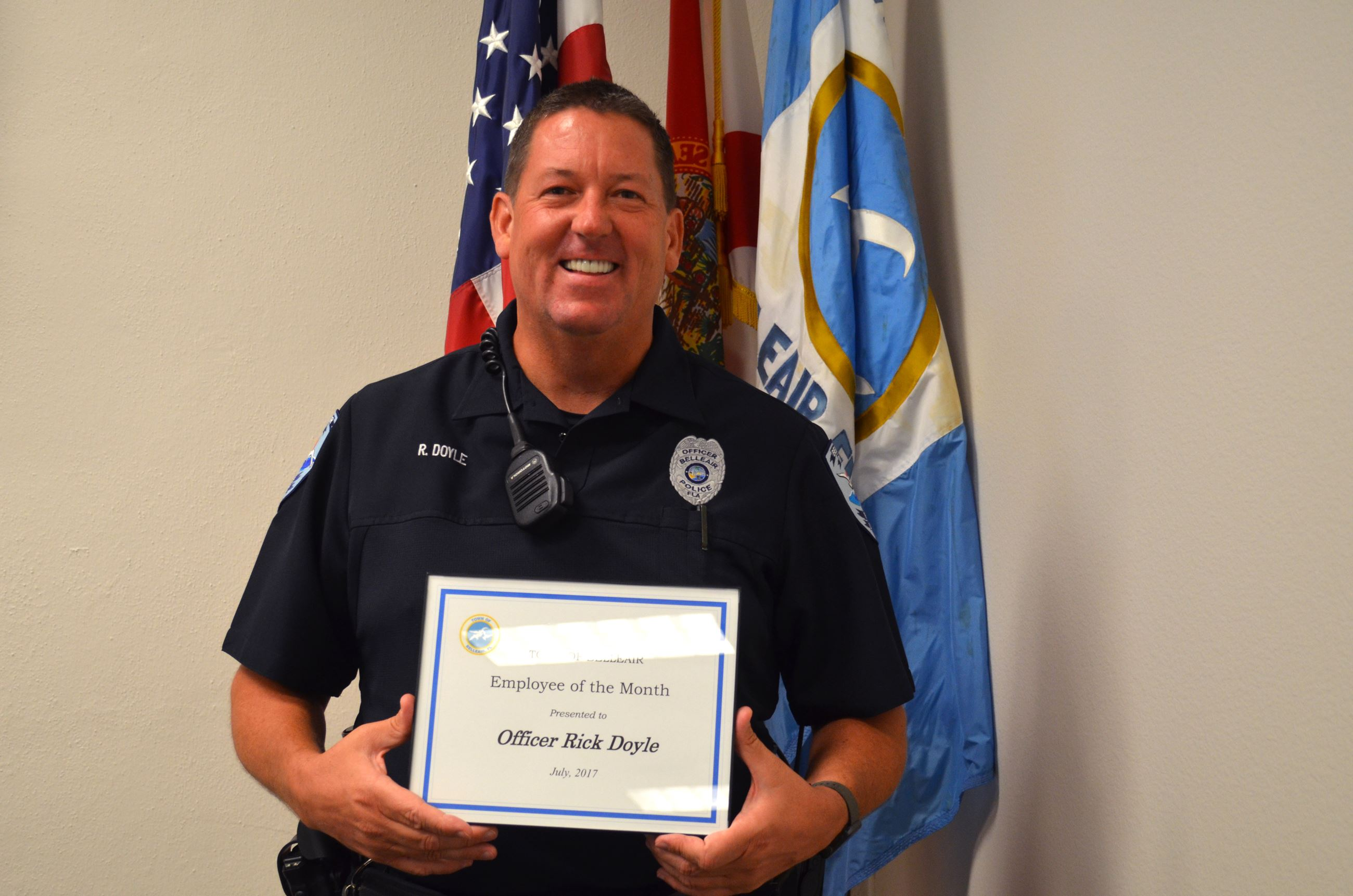Belleair Police Officer Rick Doyle smiles with his Employee of the Month Certificate for July, 2017.