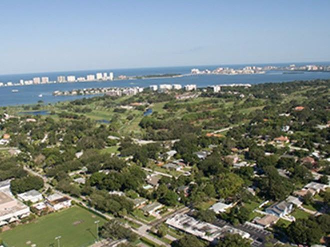 Aerial view of the Town of Belleair that shows the tops of trees and the waterfront.