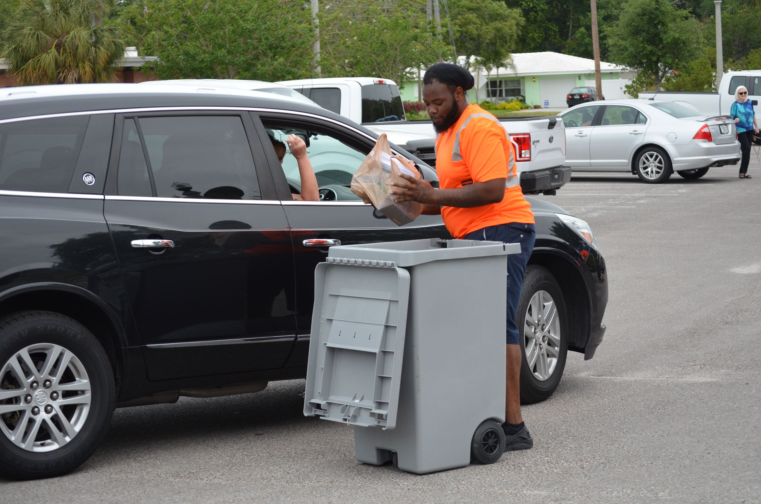 A Solid Waste Department employee collects papers from a car at a shredding event.