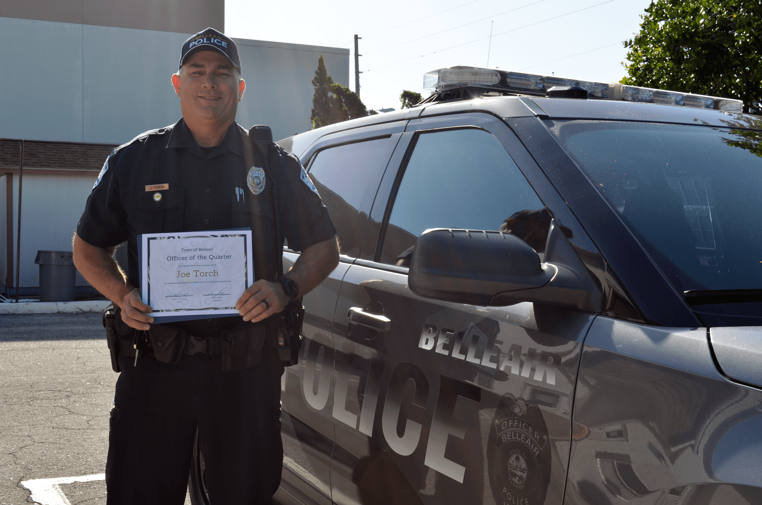 Officer Torch smiles in front of a patrol car with a certificate honoring him as officer of the quar