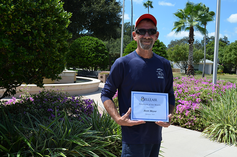 Scott holds his employee of the month certificate in Hunter Memorial Park
