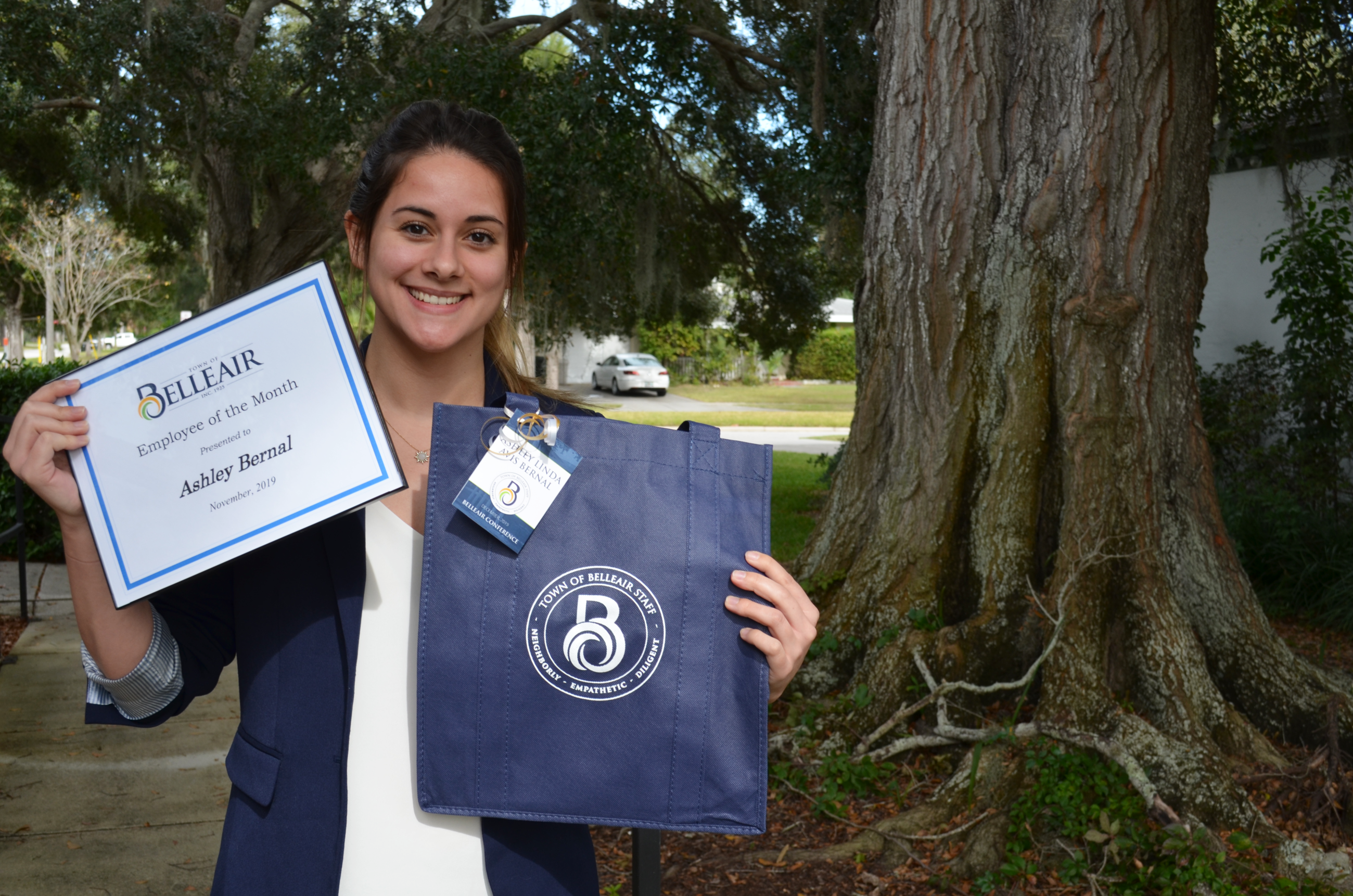 Ashley Bernal holds her Employee of the Month certificate and a branded Belleair tote she designed o