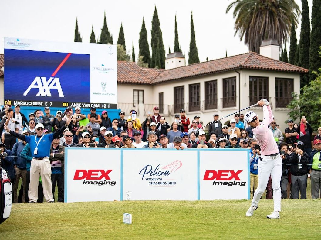 A player at an LPGA tournament tees off in front of a crowd.