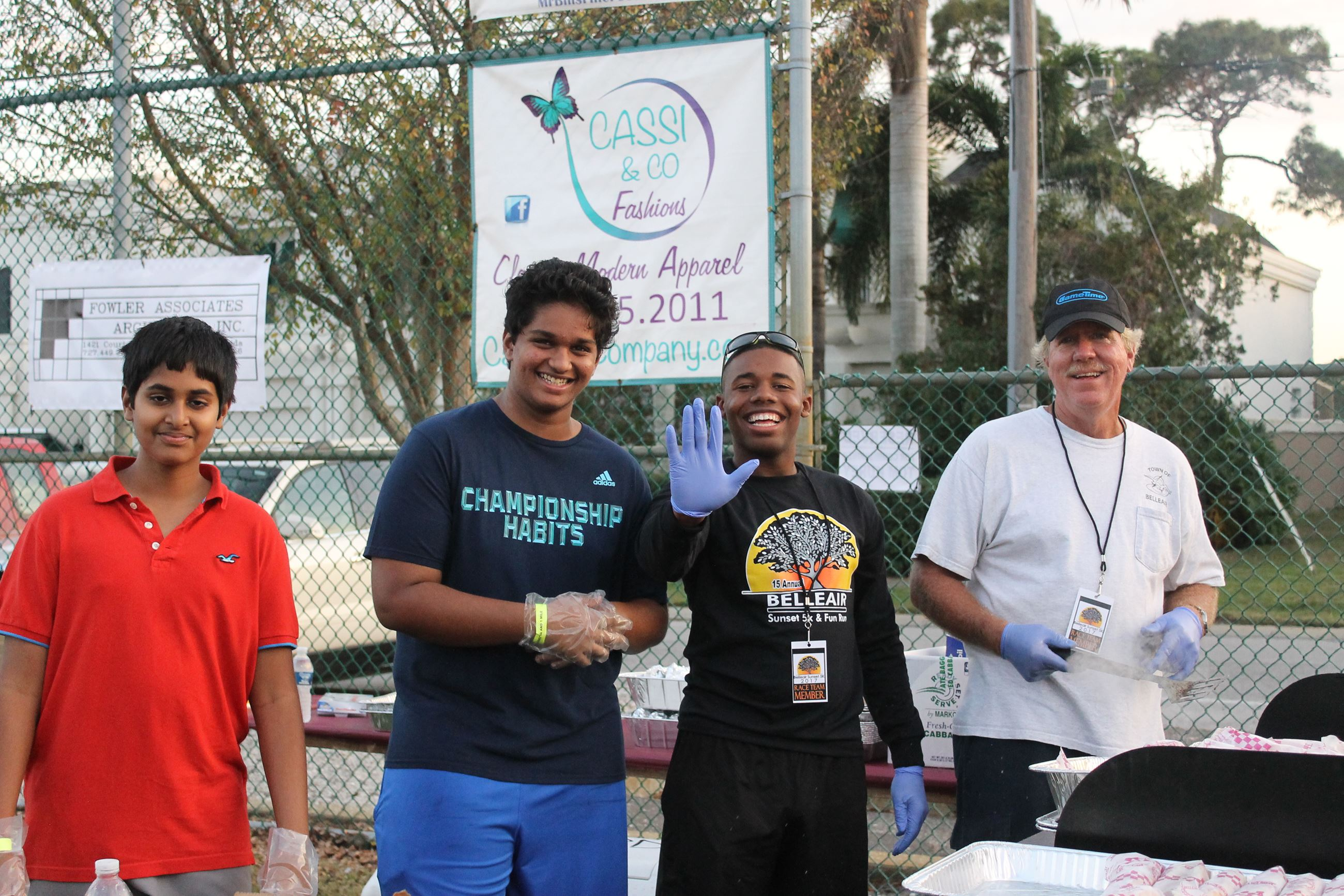 Two young volunteers assist staff making hamburgers and hot dogs at the Sunset 5K & Fun Run after pa