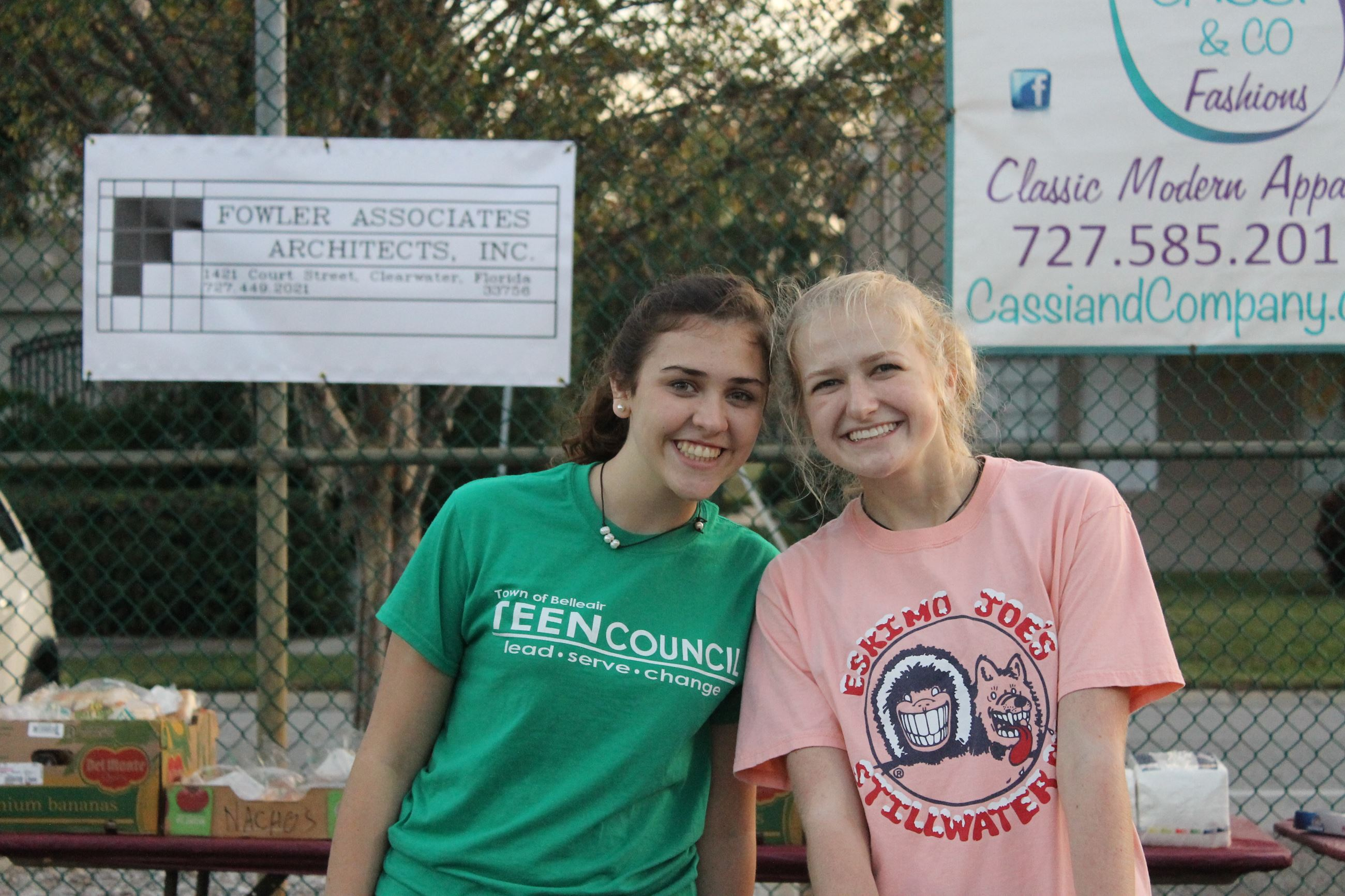 Two teenagers smile for a picture while volunteering at the Belleair Sunset 5K and Fun Run after par