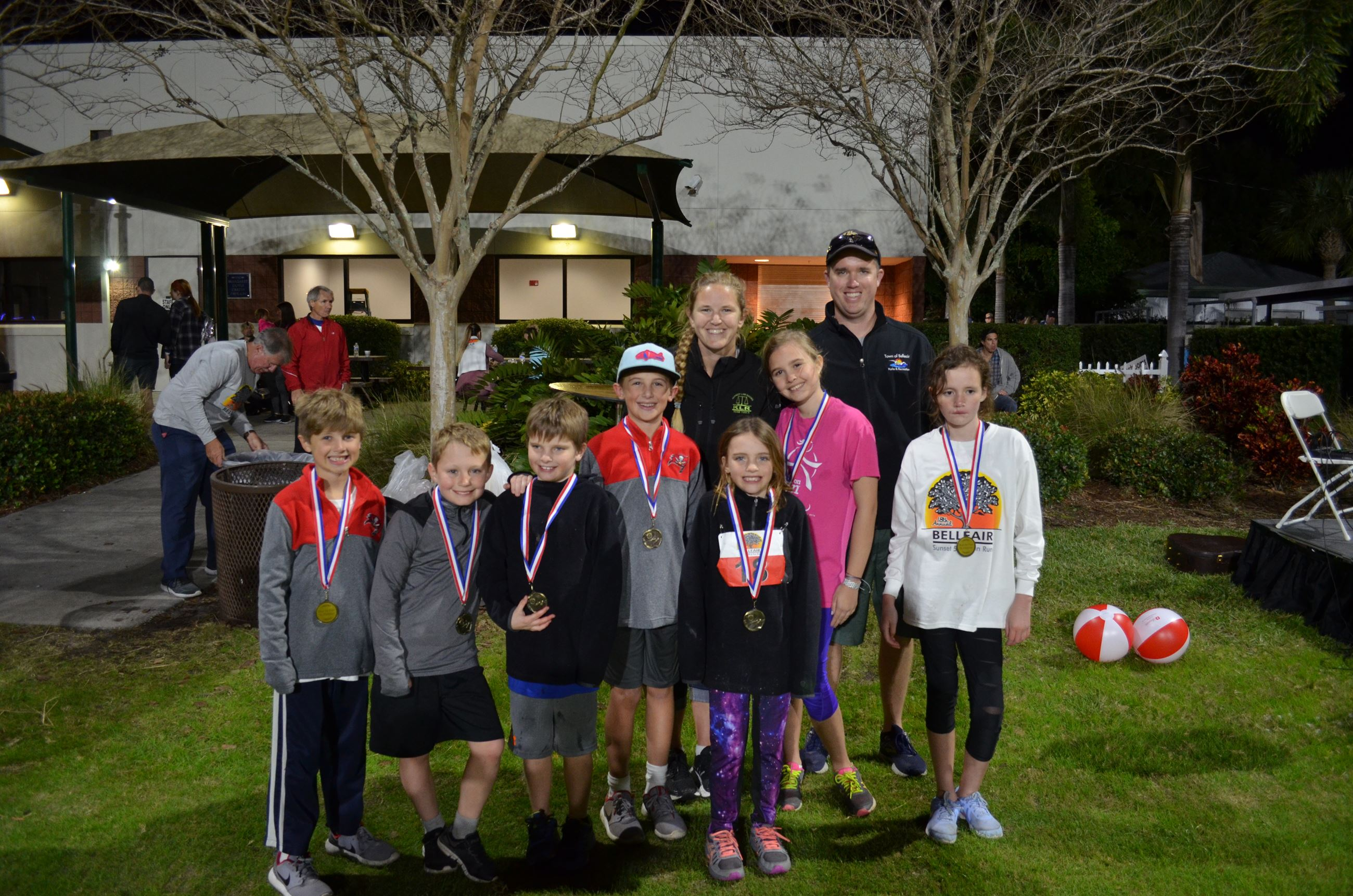 A group of seven children and two adults smile with their medals after completing a 5K race.