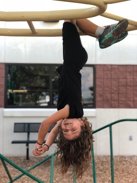 A girl hanging upside down from a set of monkey bars on a playground, smiling.