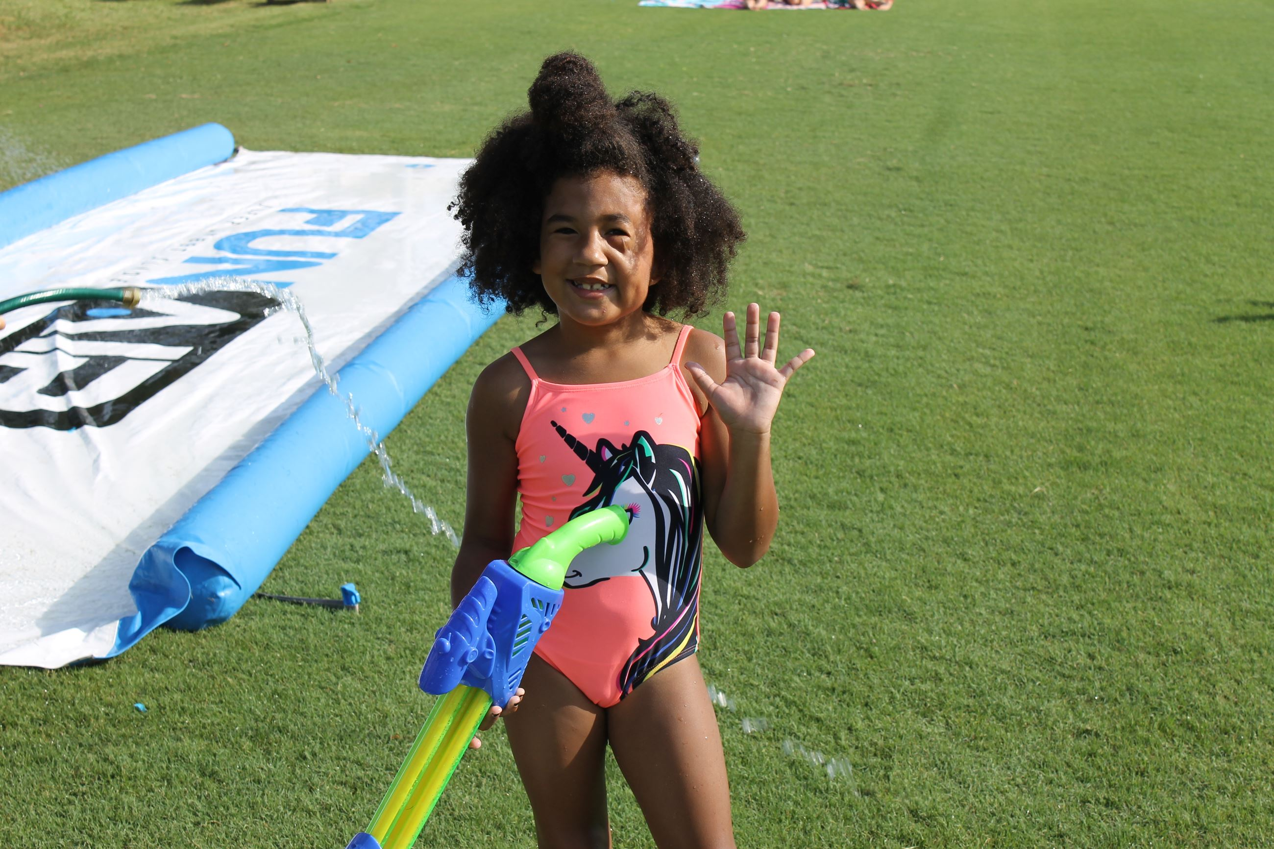 Girl smiles while holding a water gun