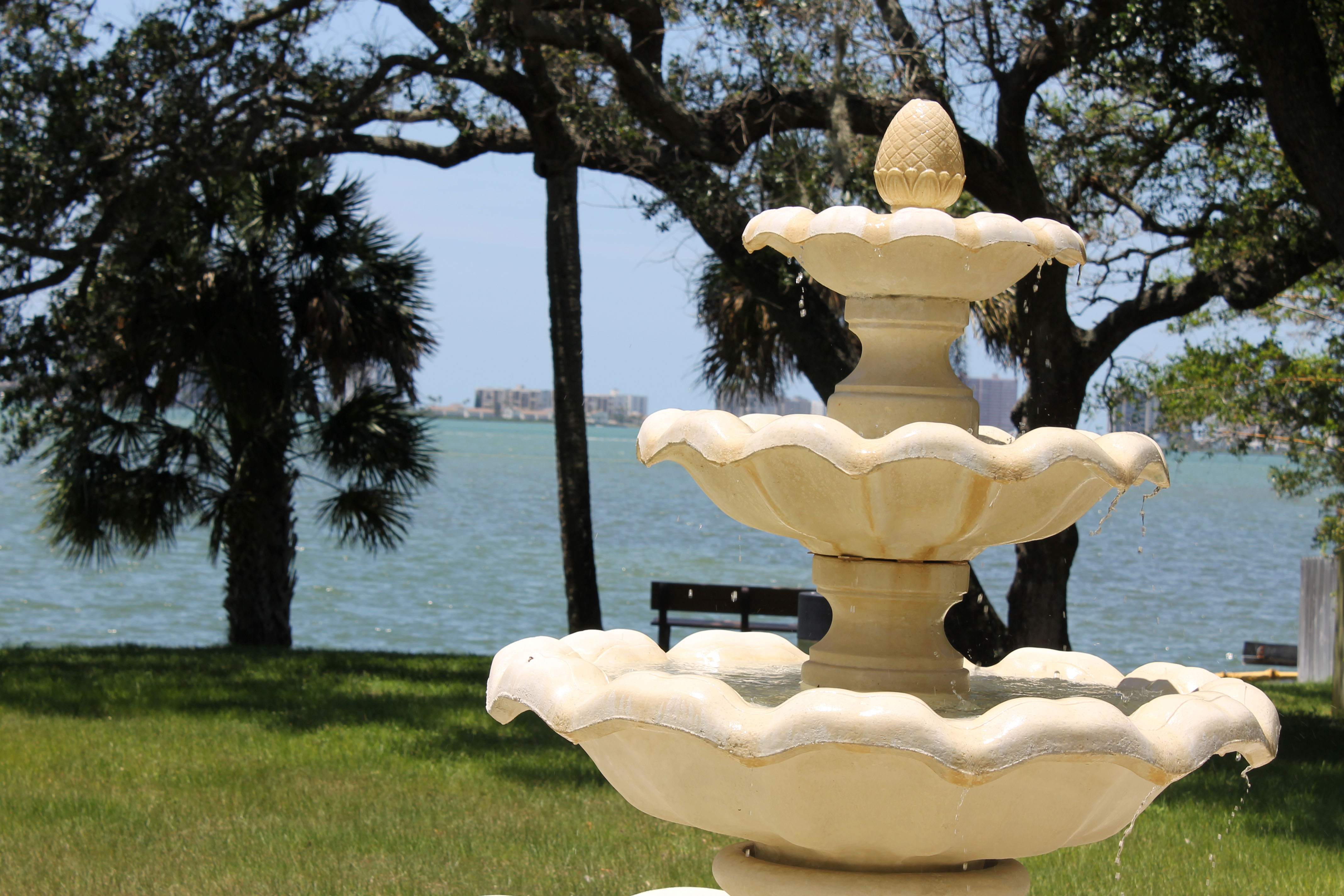 A white, three-tiered fountain in Thompson Park with trees and the Clearwater Harbor behind