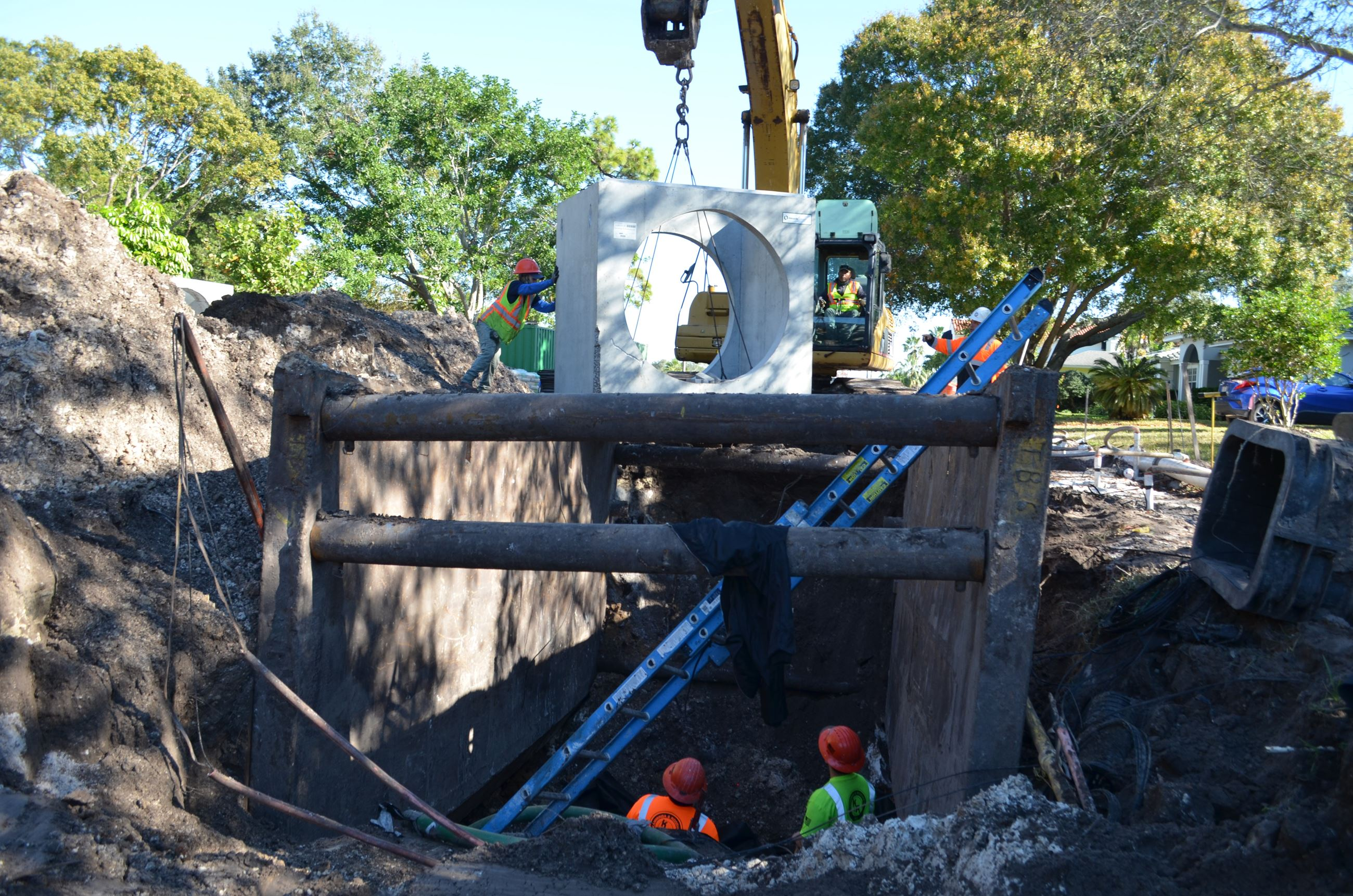 Contractors use a crane to lower a drainage device underground at the Palmetto North Roadway Project