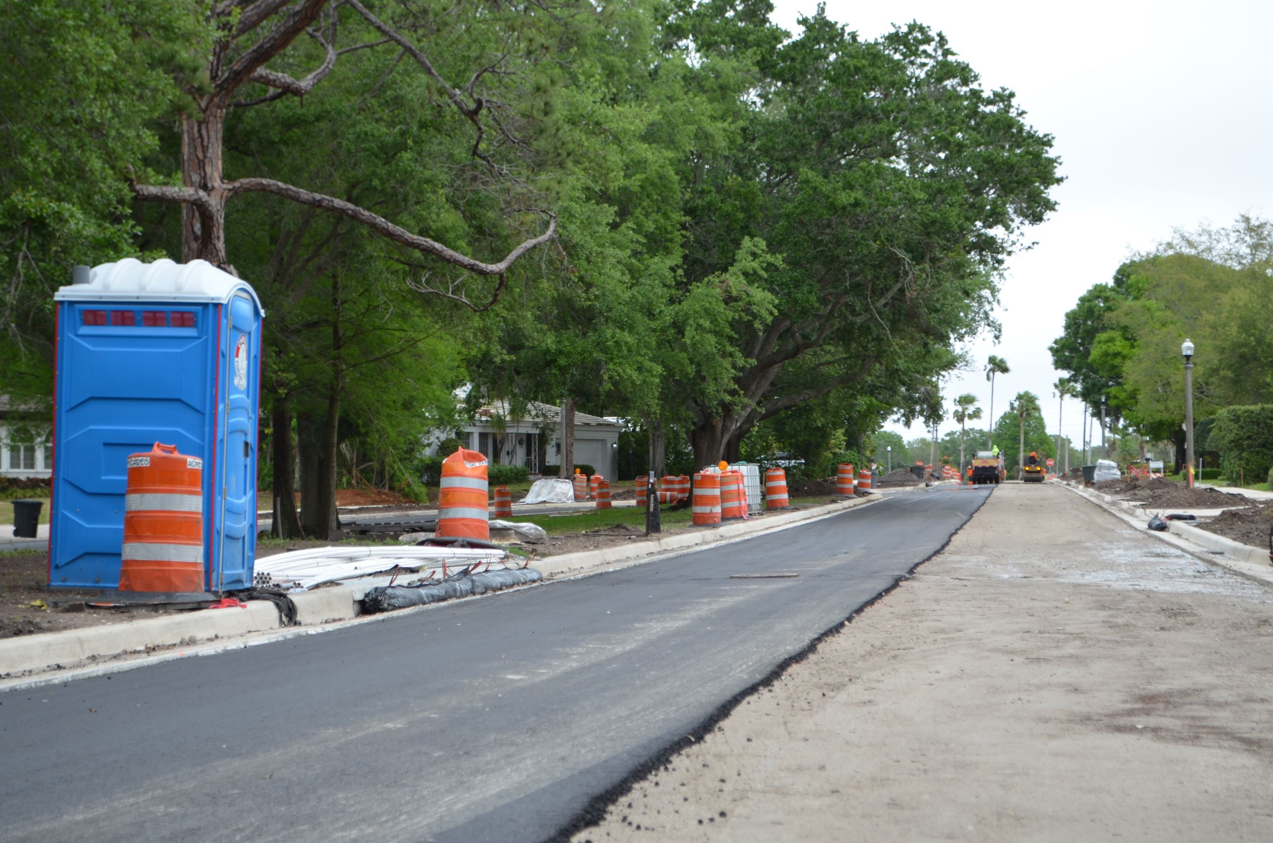 One lane of Palmetto Road is paved with fresh asphalt while trucks work on other sections